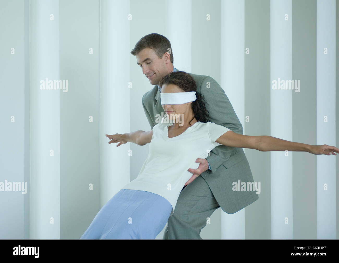 Businessman catching blindfolded woman - Stock Image