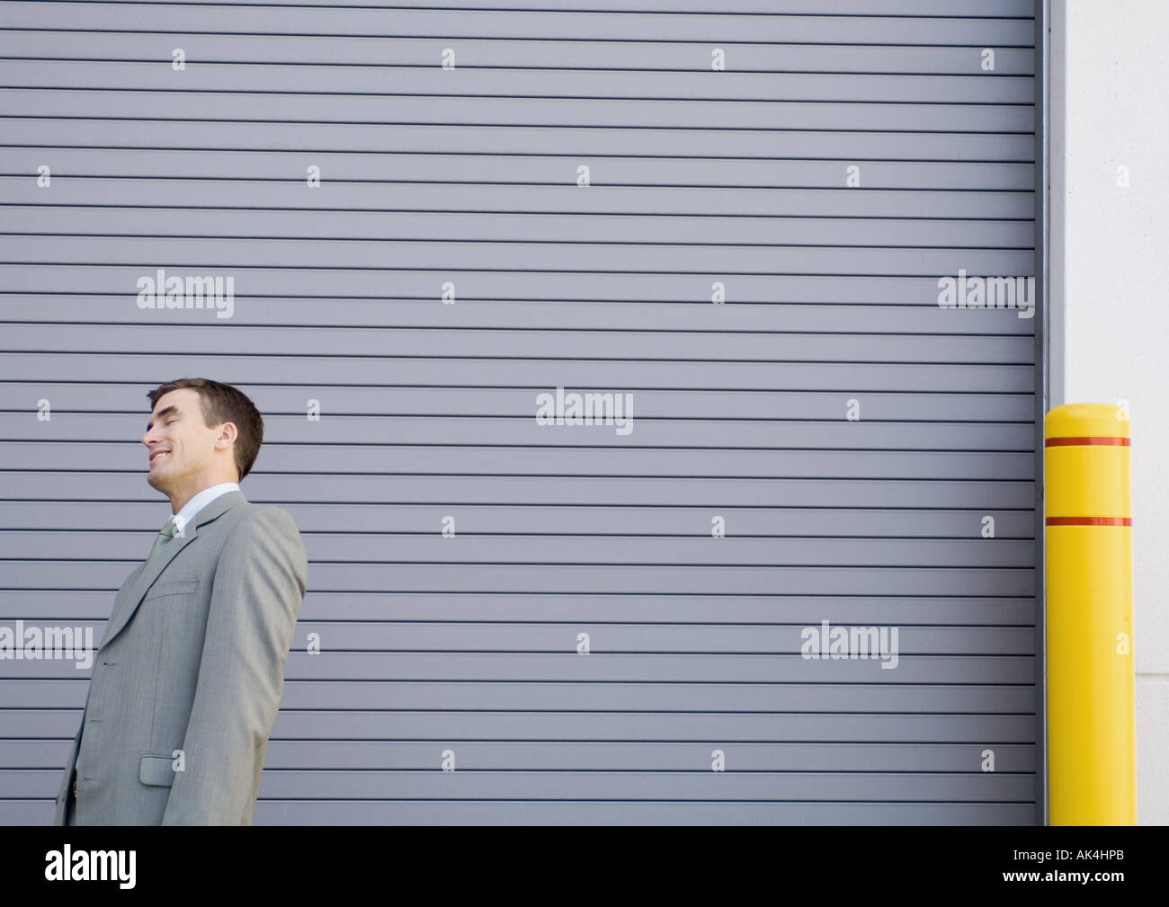 Businessman standing and smiling, leaning backwards with eyes shut - Stock Image