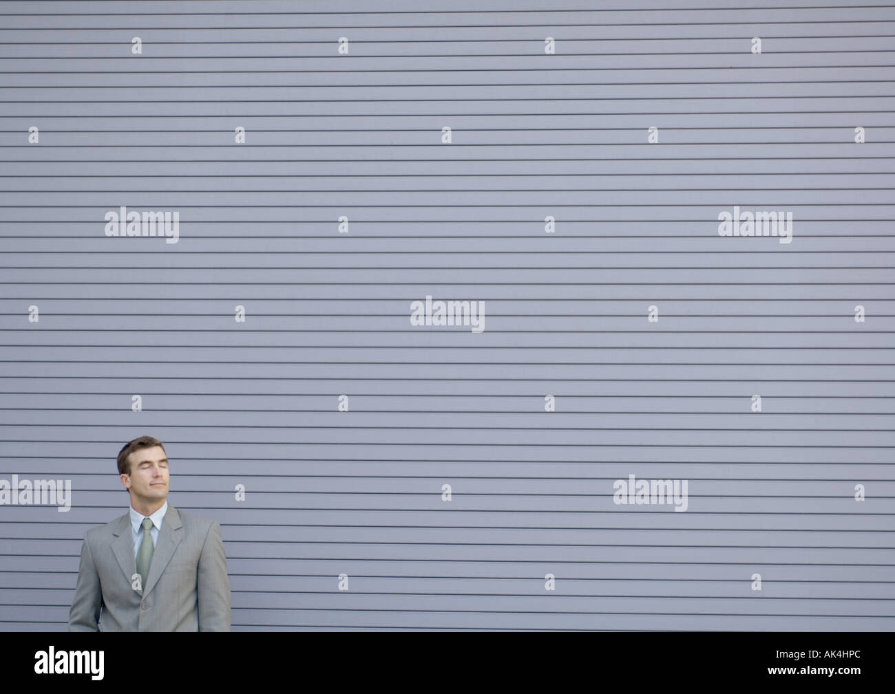 Businessman smiling, eyes shut - Stock Image