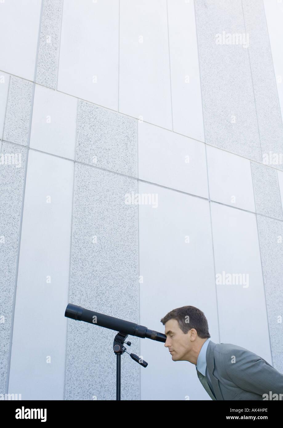 Businessman looking through telescope - Stock Image