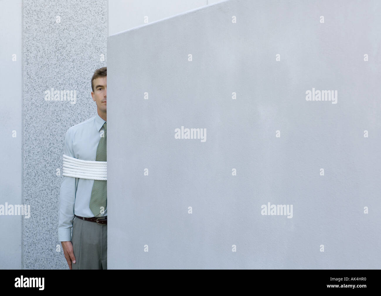Businessman tied up, standing partially hidden behind wall - Stock Image