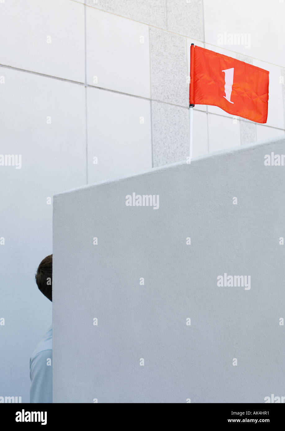 Part of man visible behind wall and red flag with number '1' overhead - Stock Image