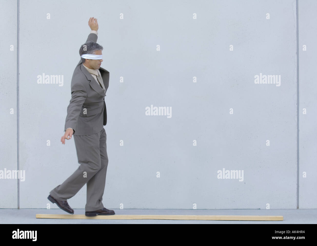 Blindfolded businessman walking on wooden plank - Stock Image