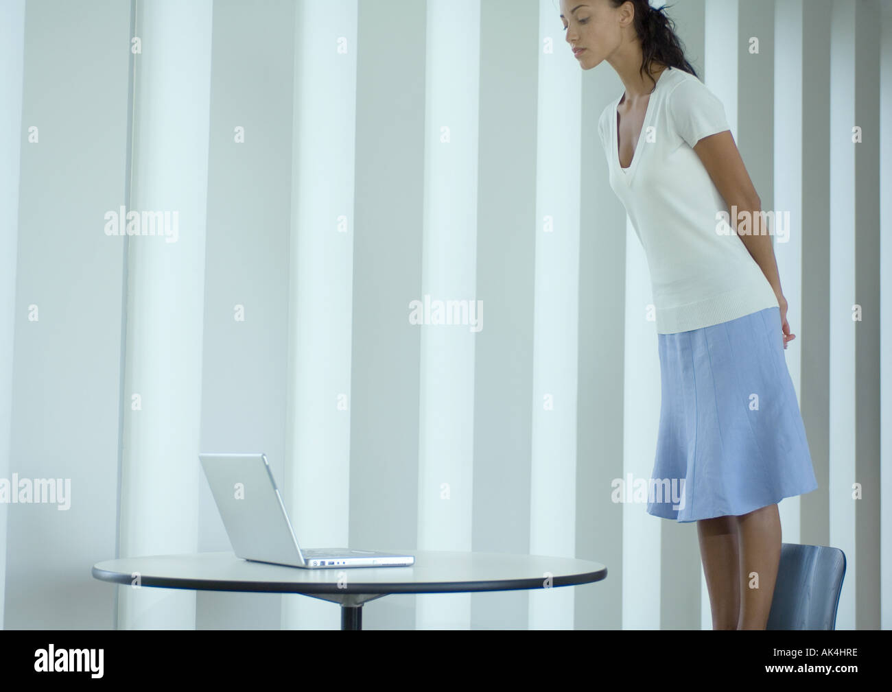 Woman standing on chair, looking down at laptop - Stock Image