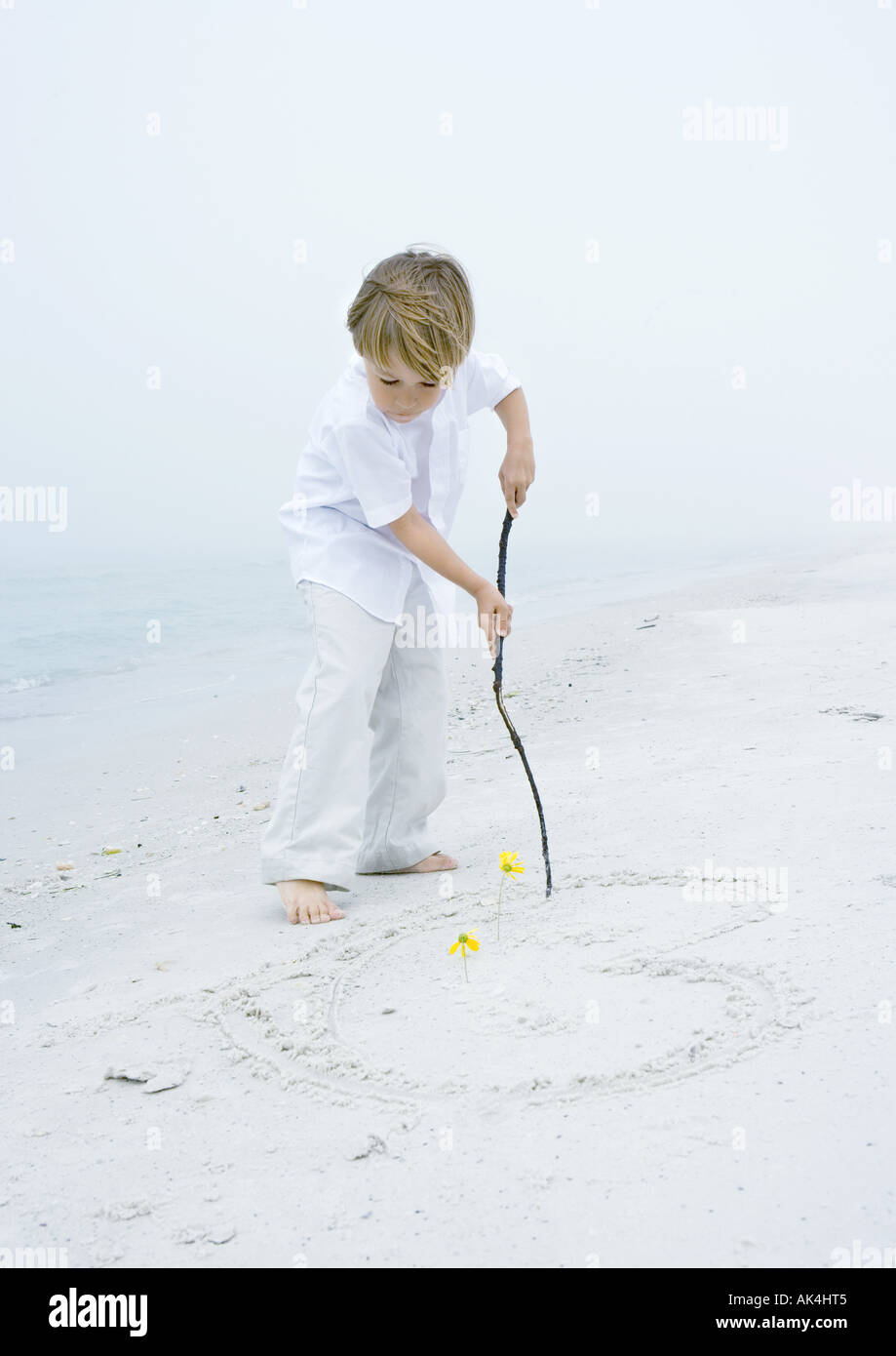 Little boy drawing heart in the sand at the beach - Stock Image