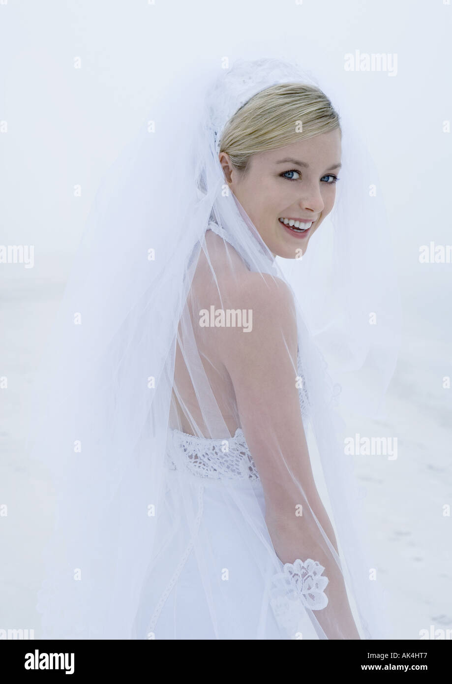 Bride looking over shoulder at camera - Stock Image