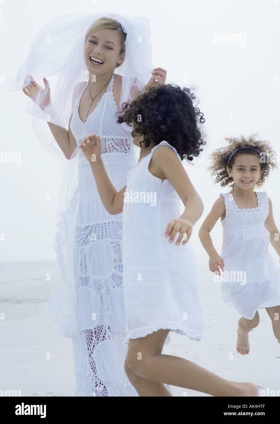 Two little girls running around bride on beach - Stock Image
