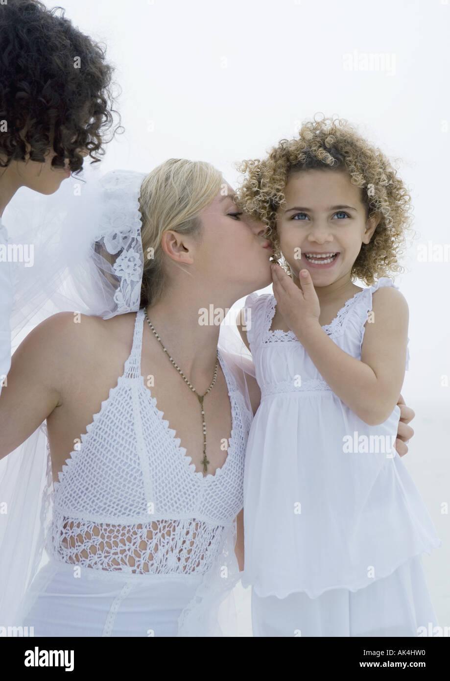 Bride kissing little girl's cheek - Stock Image