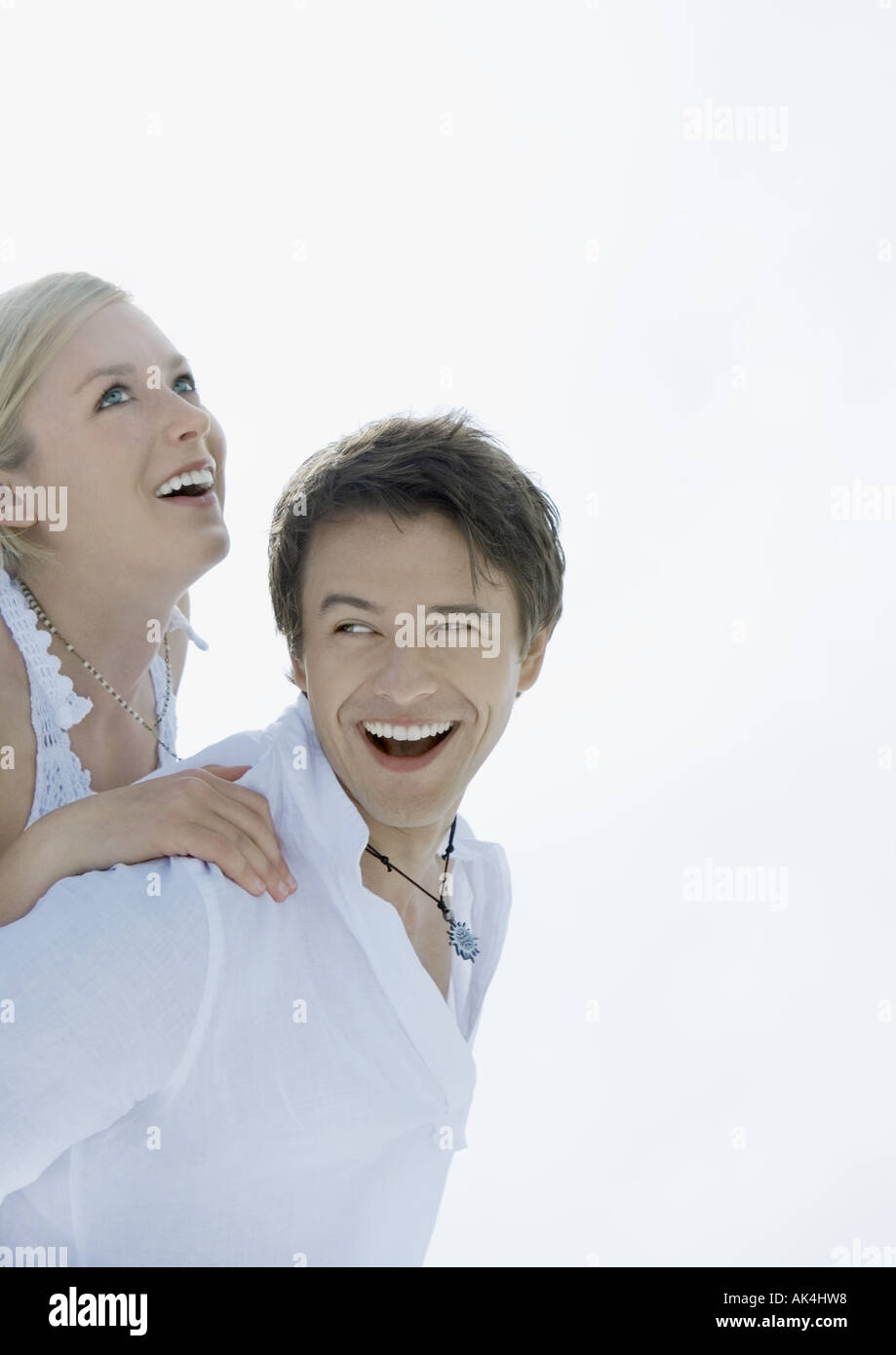 Woman on man's back, both laughing - Stock Image