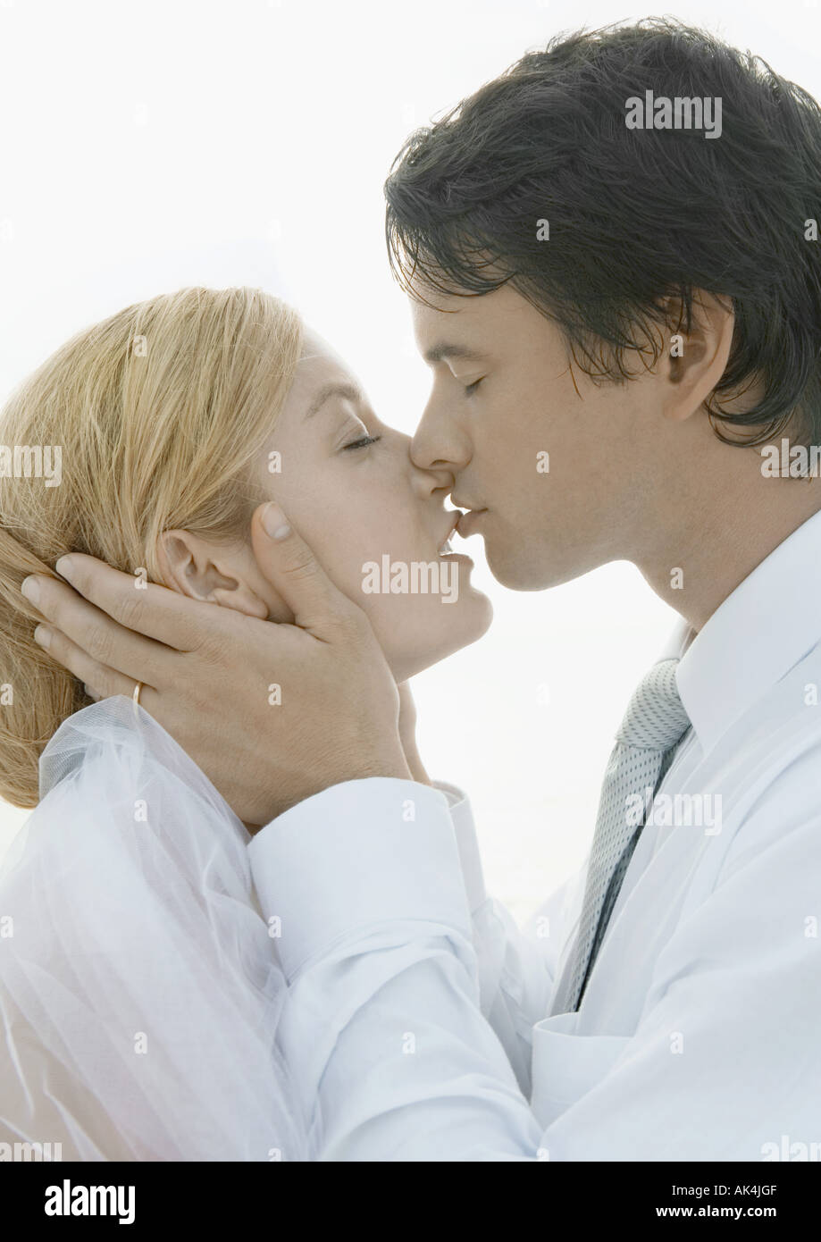 Bride and groom kissing, portrait - Stock Image