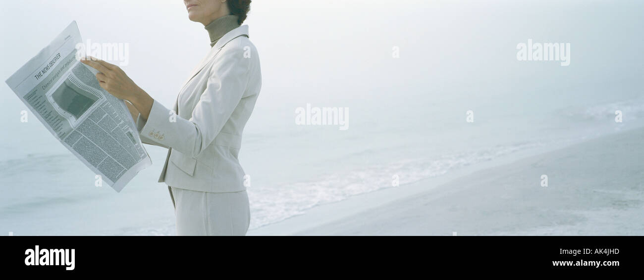 Businesswoman reading newspaper on beach, cropped - Stock Image