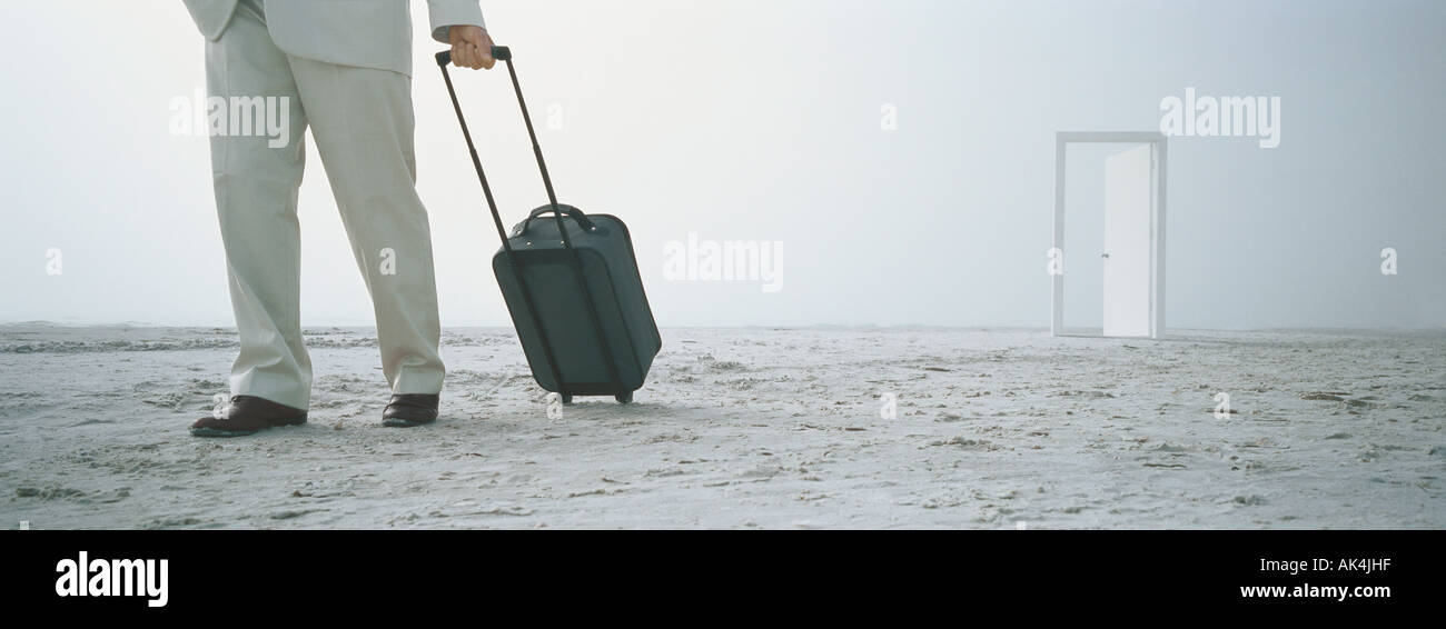 Businessman with suitcase on beach, doorway in background - Stock Image