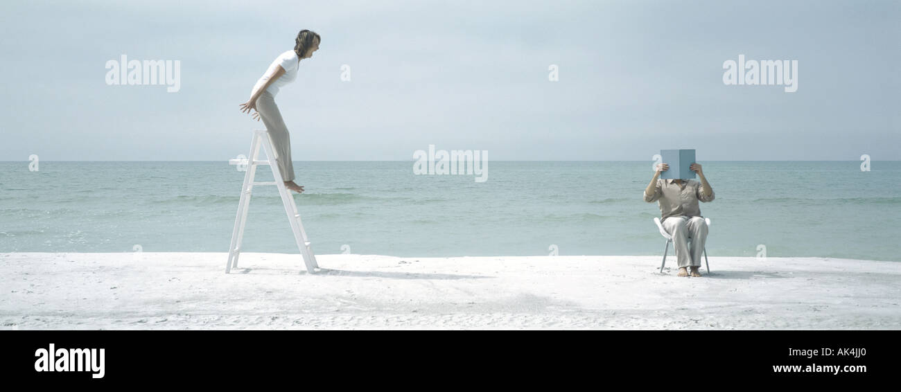 On beach, woman standing on ladder shouting at man who sits, covering face - Stock Image
