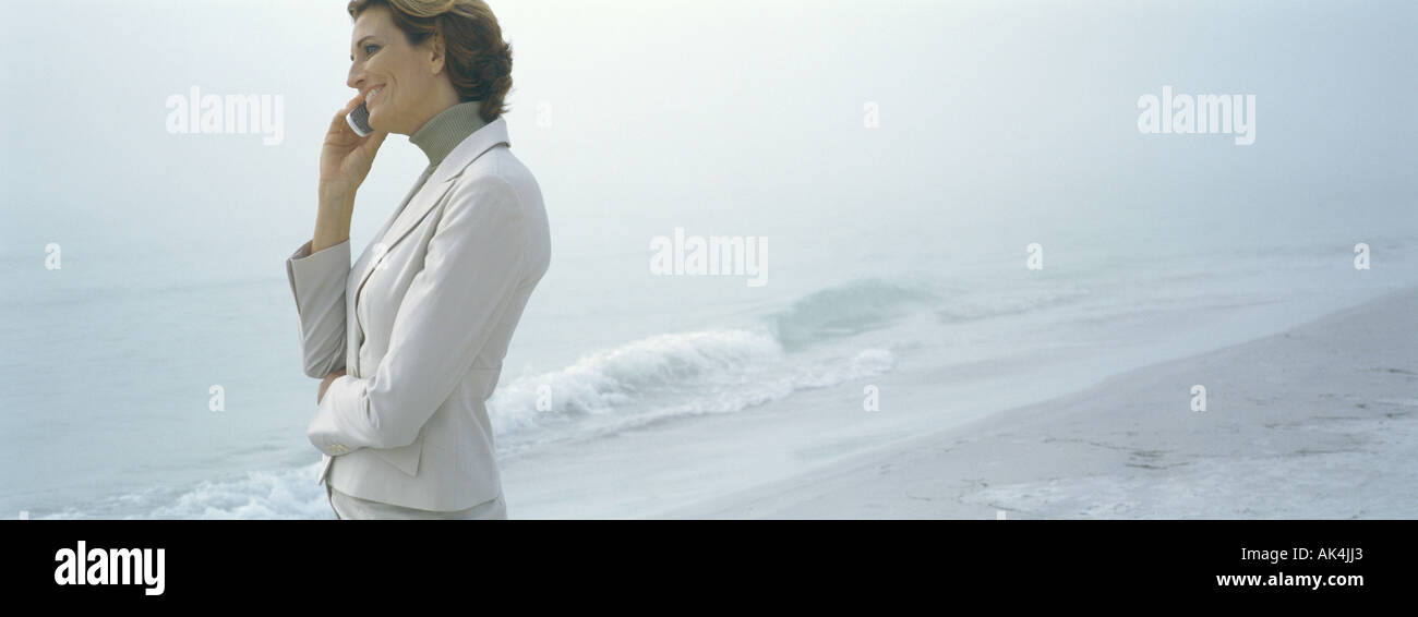 Businesswoman using cell phone on beach, smiling - Stock Image