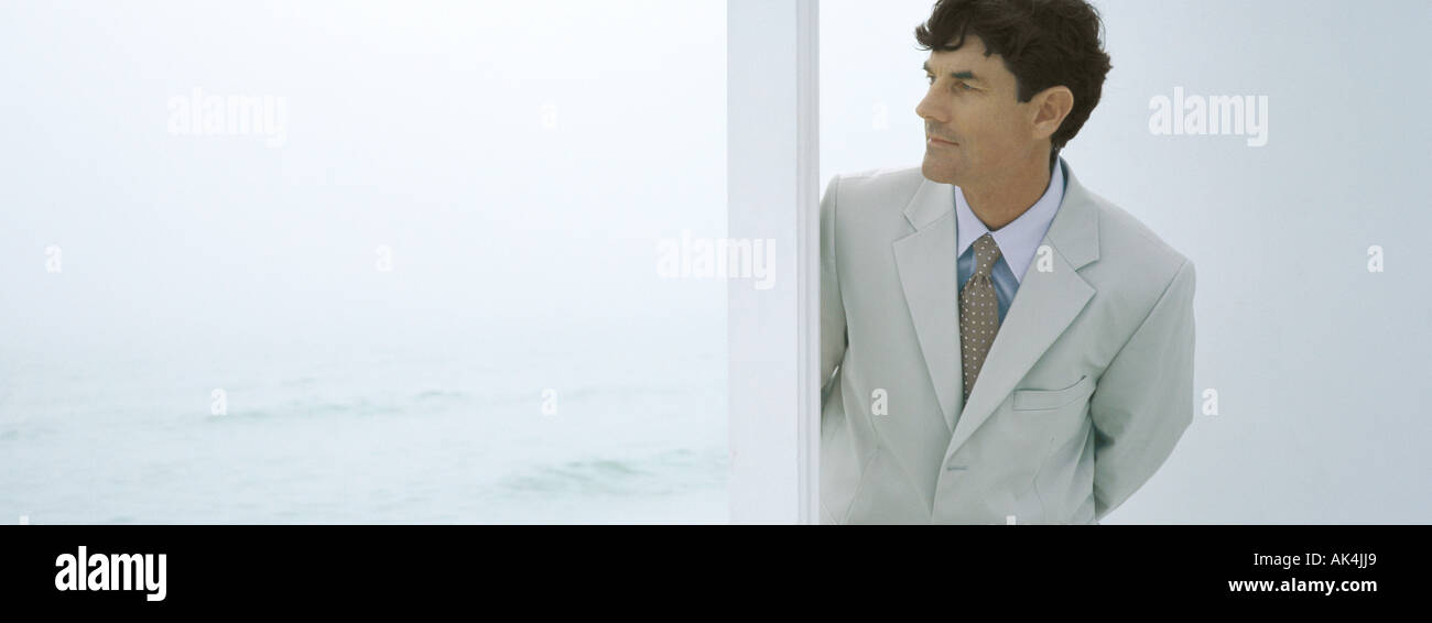 Businessman coming through doorway, sea in background - Stock Image