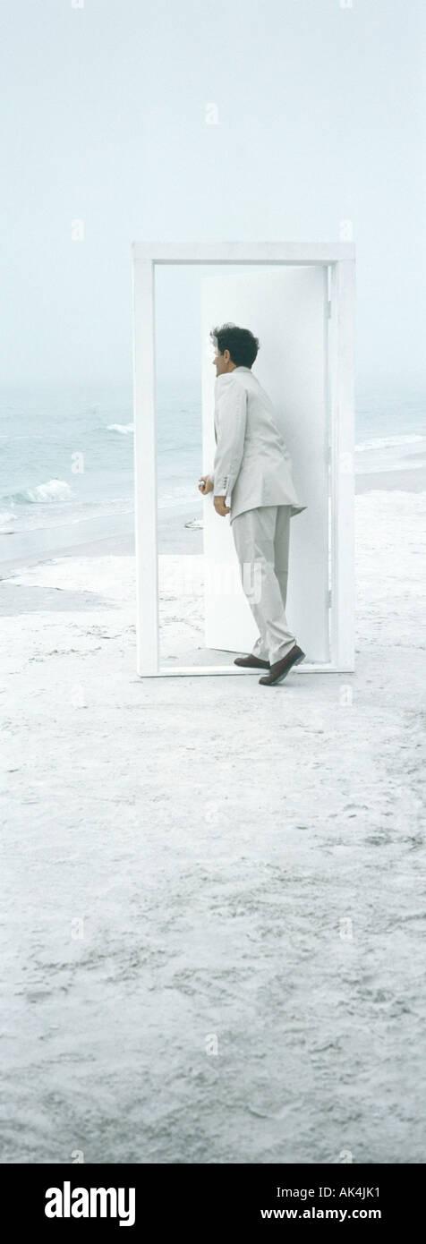 On beach, businessman opening door - Stock Image