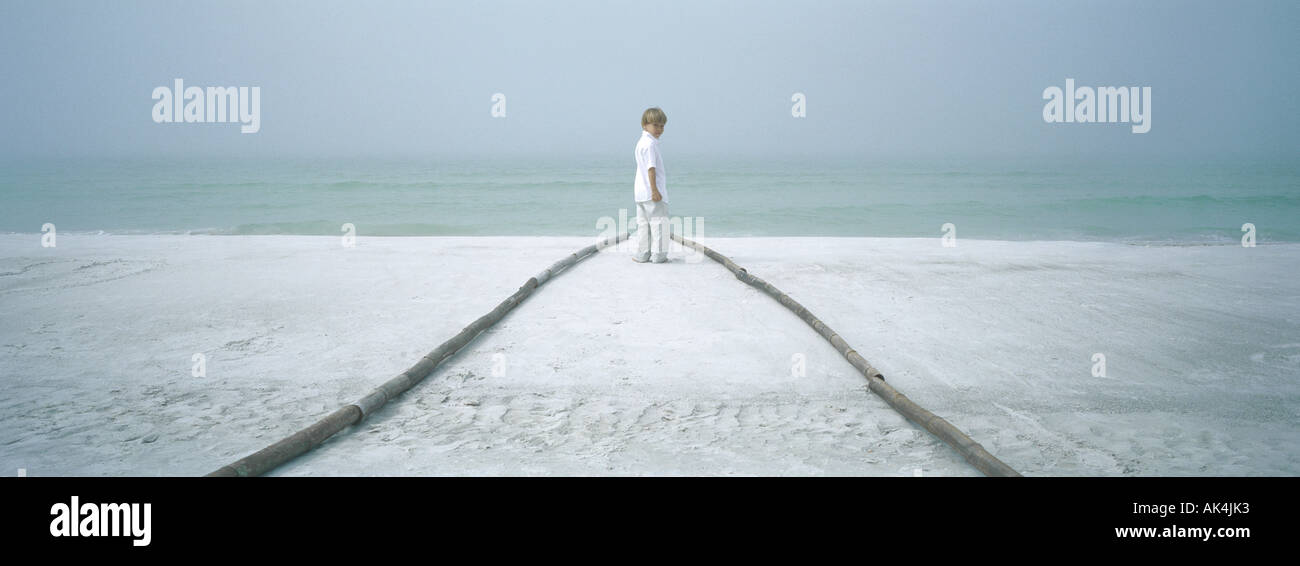 Boy standing at end of path on beach, looking over shoulder - Stock Image