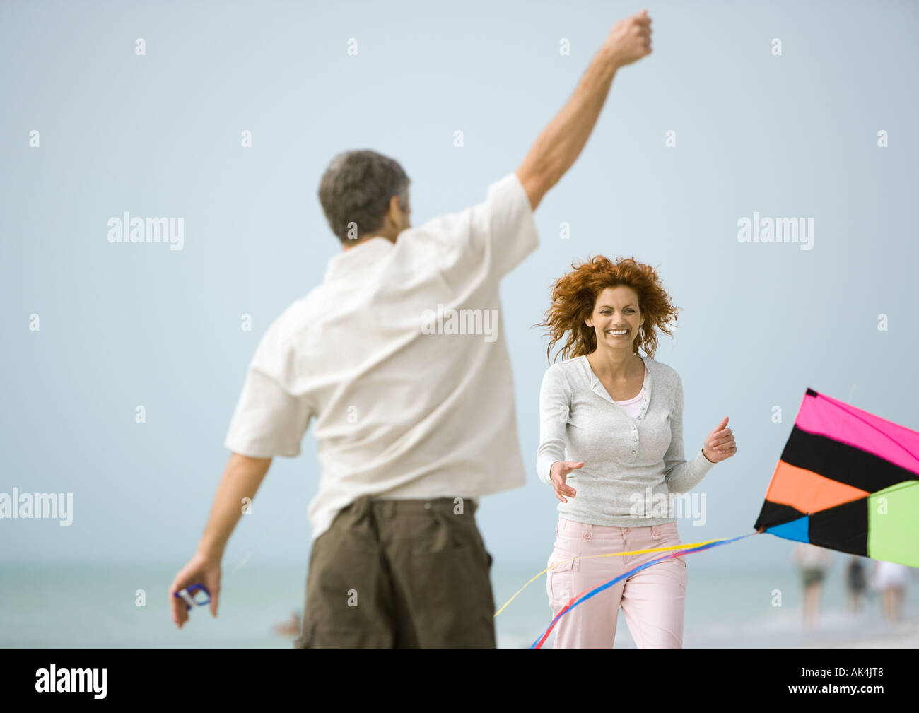 Couple with kite on beach - Stock Image