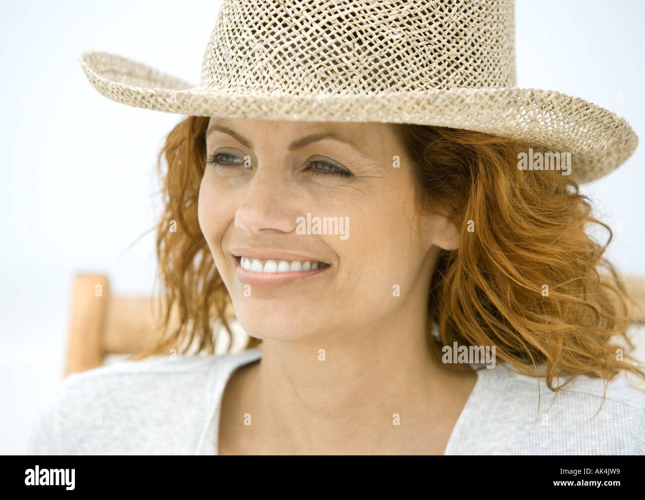 Woman sitting in beach chair, wearing sun hat - Stock Image