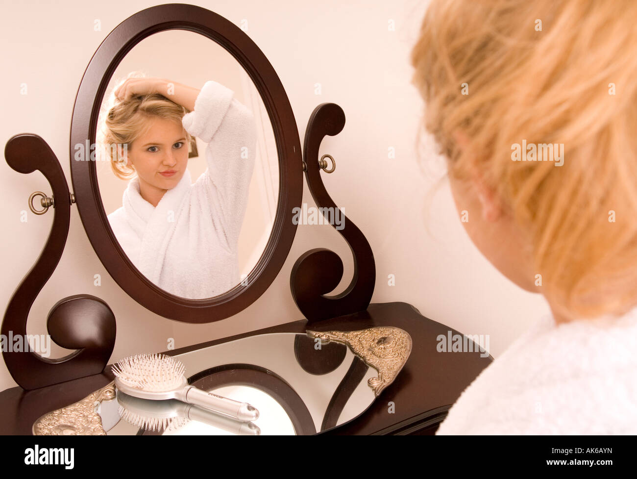 Caucasian Teen Girl (15-17) Looking in Mirror and Rolling Hair with Curlers USA - Stock Image