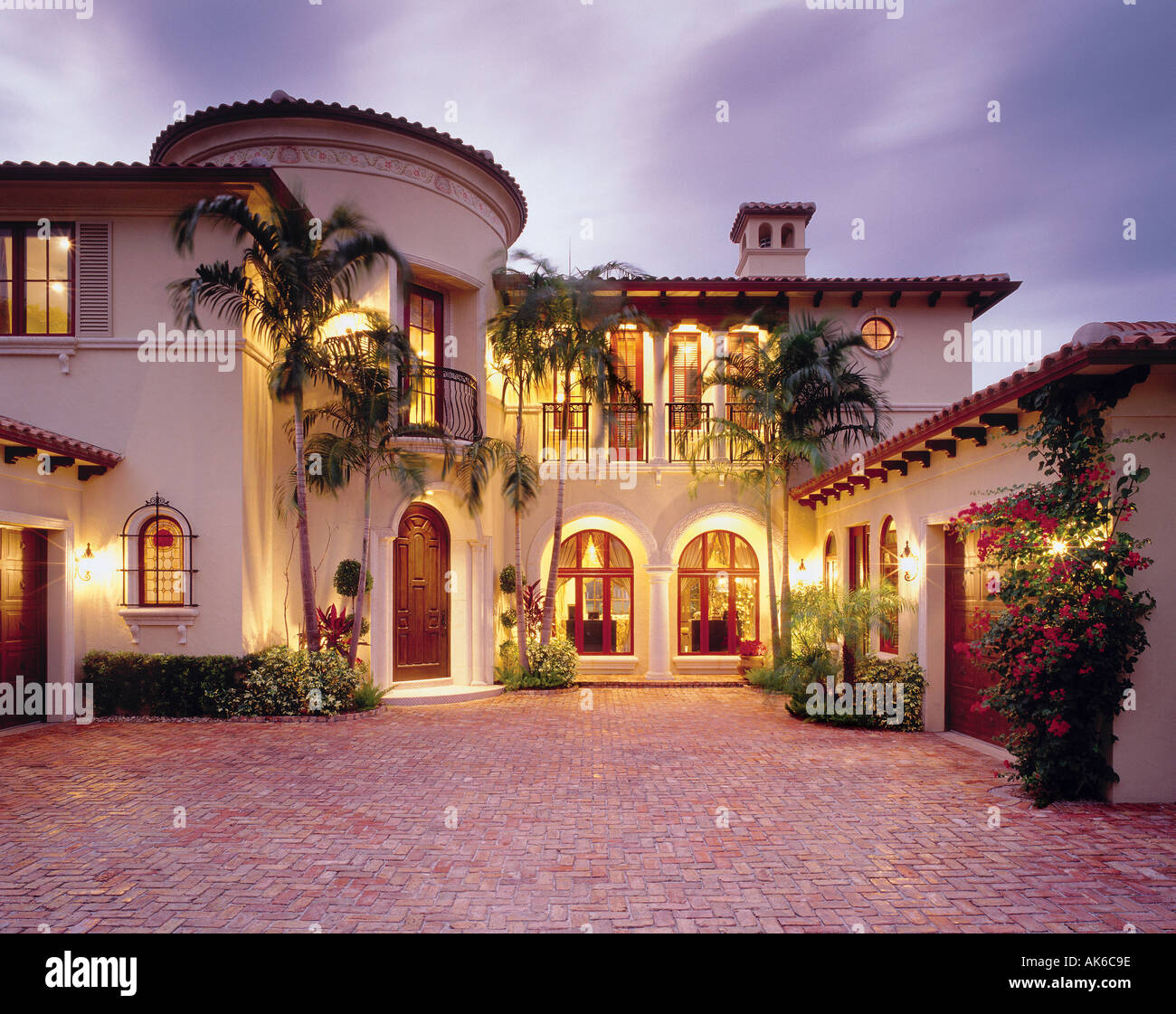 Mediterranean single family home with brick courtyard in Boca Raton, Florida. Features bougainvillea plants and palm trees. - Stock Image
