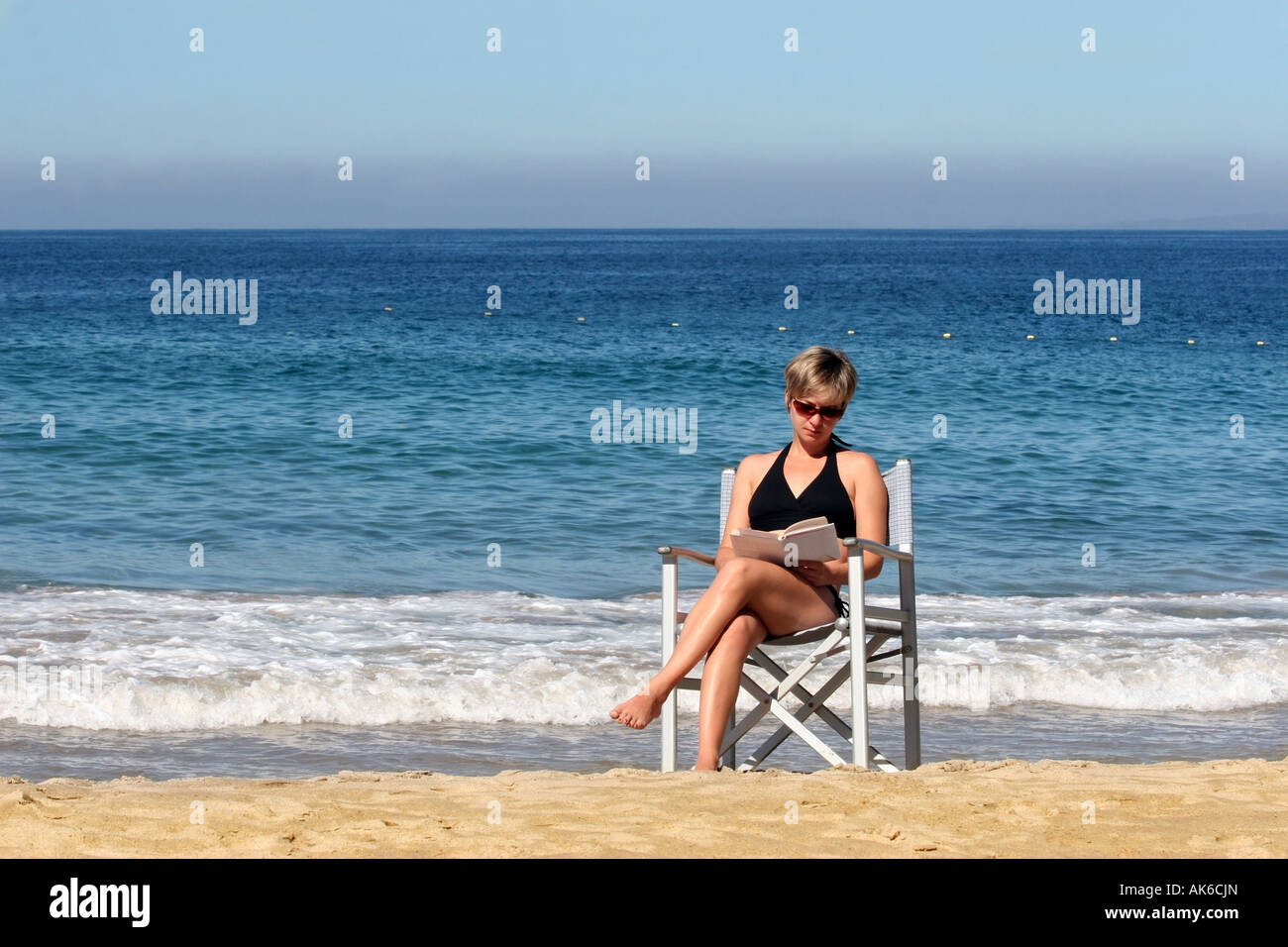 Woman relaxing on a beach - Stock Image