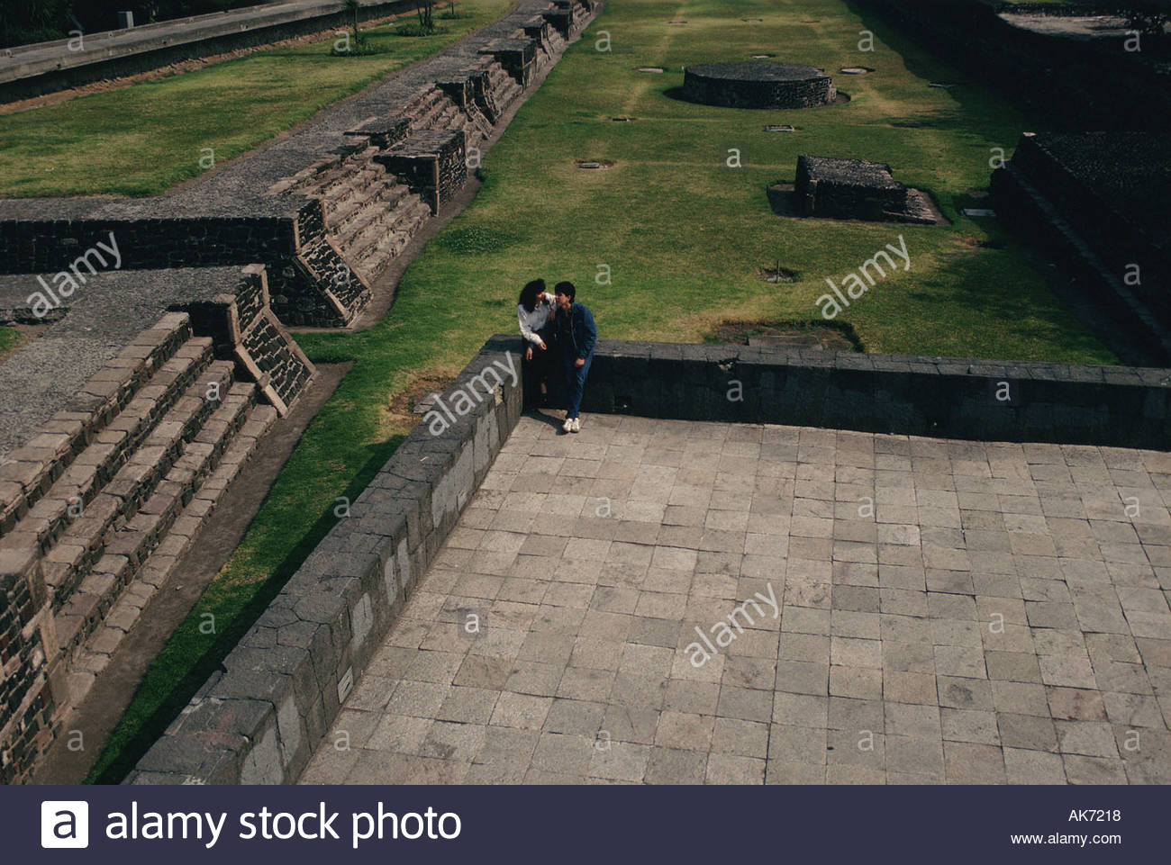MEXICO Mexico City Plaza of the Three Cultures young couple sitting in the courtyard of a pyramid in the Aztec city: Tlatelolco - Stock Image