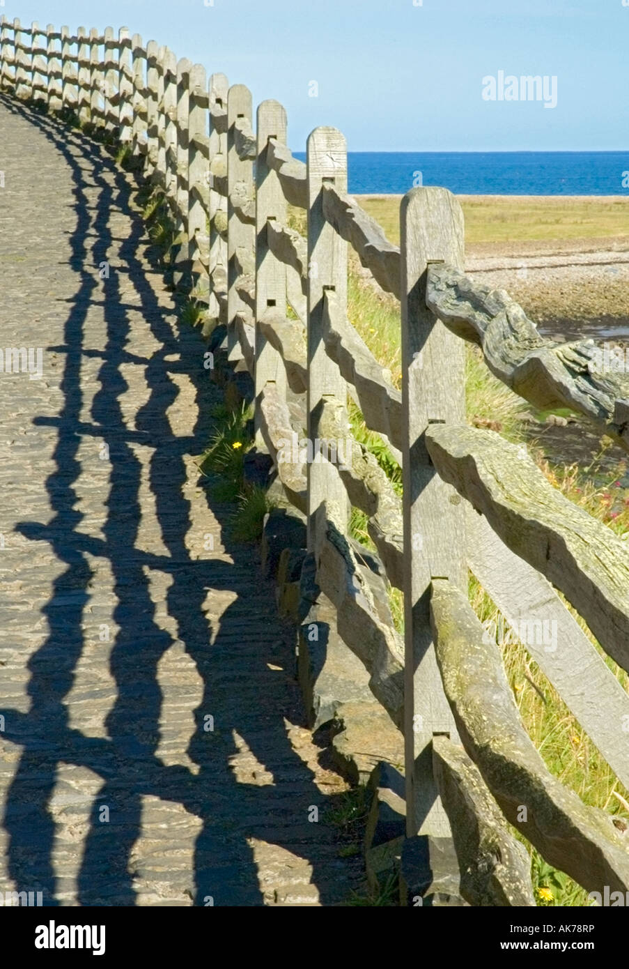 Rustic wooden fence bordering a steep path and casting a strong shadow - Stock Image