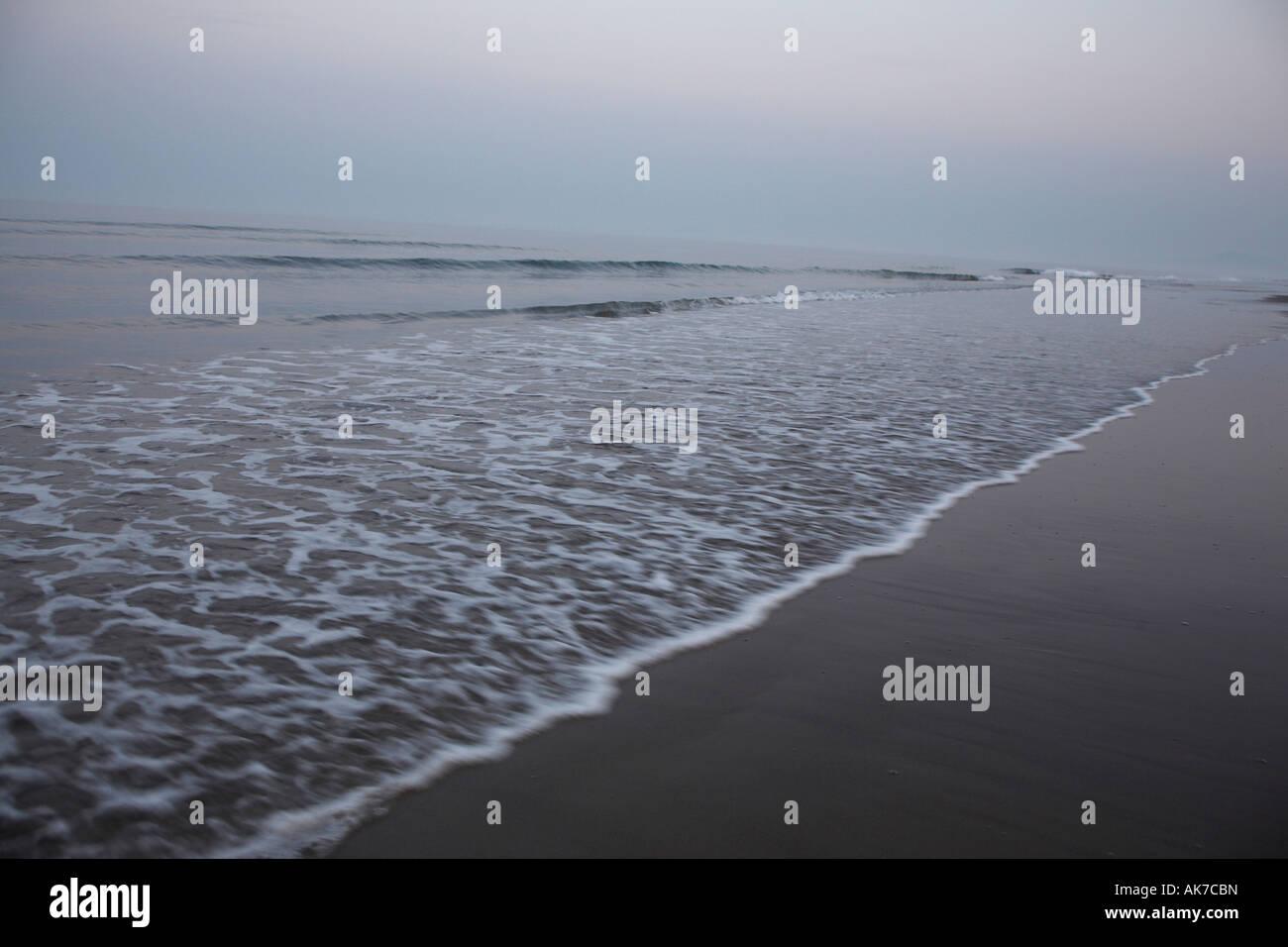Waves rushing over sand Stock Photo