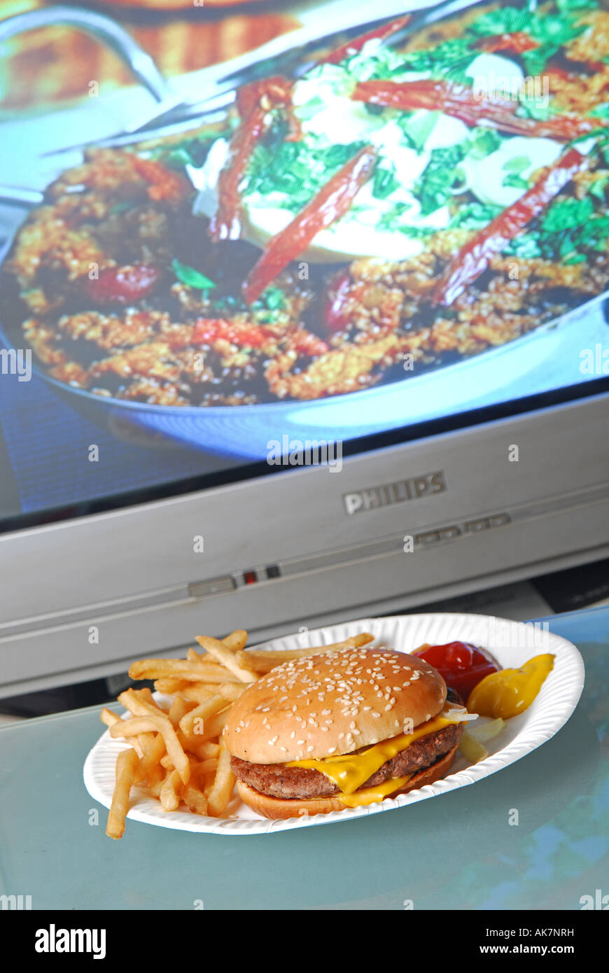 Concept shot to show unhealthy fast food TV dinner in front of television cookery programme showing healthy fresh - Stock Image