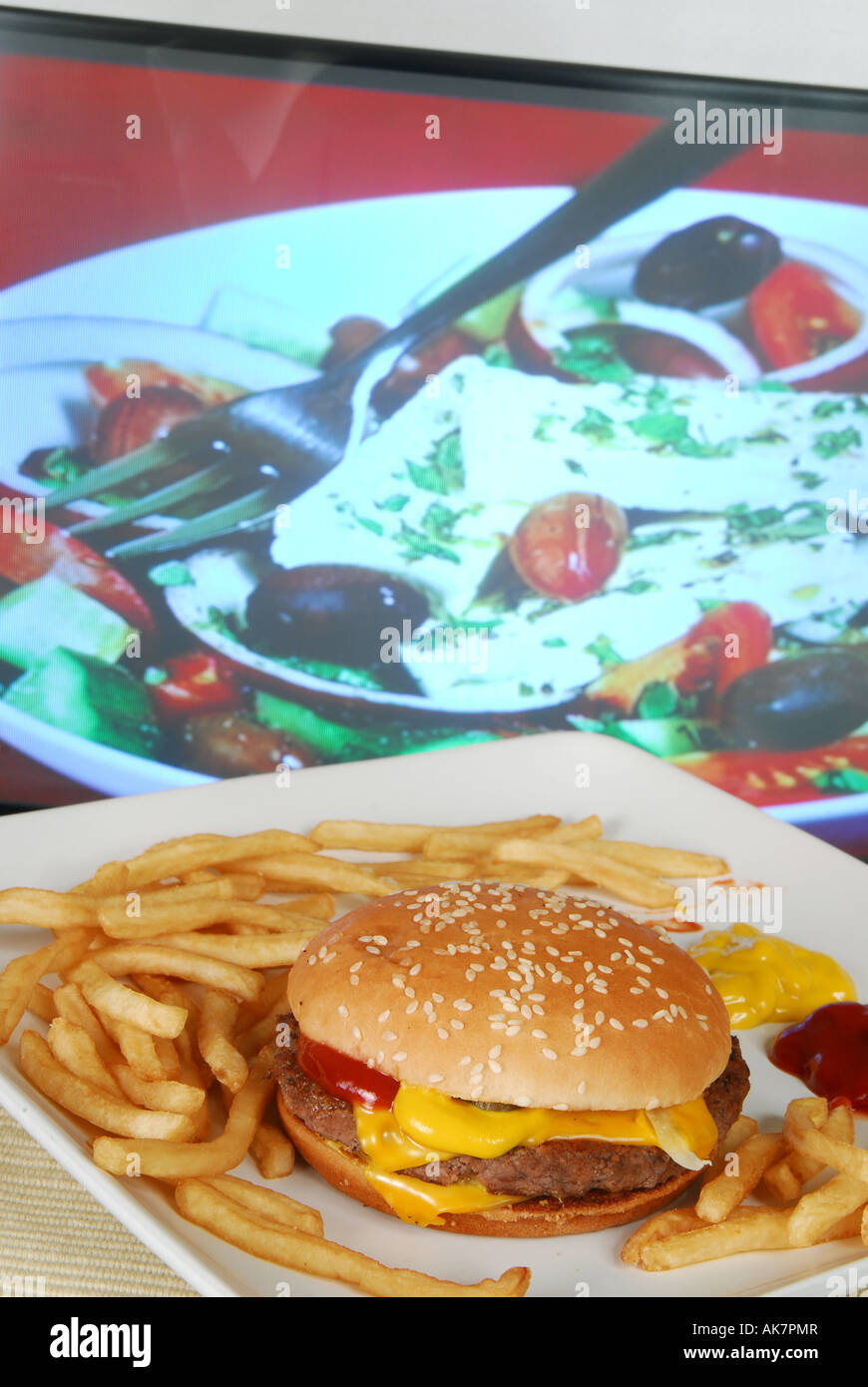 Concept shot to show unhealthy fast food TV dinner in front of television cookery programme showing healthy Greek - Stock Image