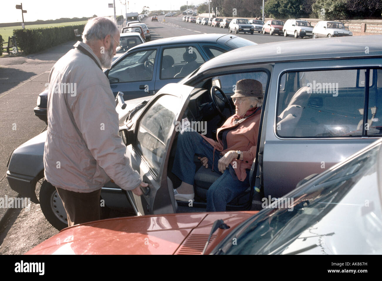 elderly son assisting mother out of the car - Stock Image