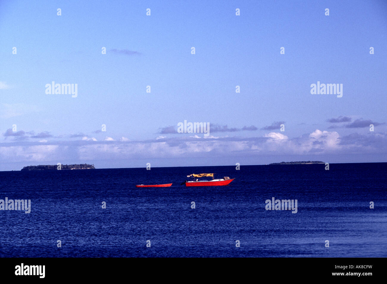 A red taxi boat crosses the sea between the Islands of Kiribati, South Pacific. - Stock Image