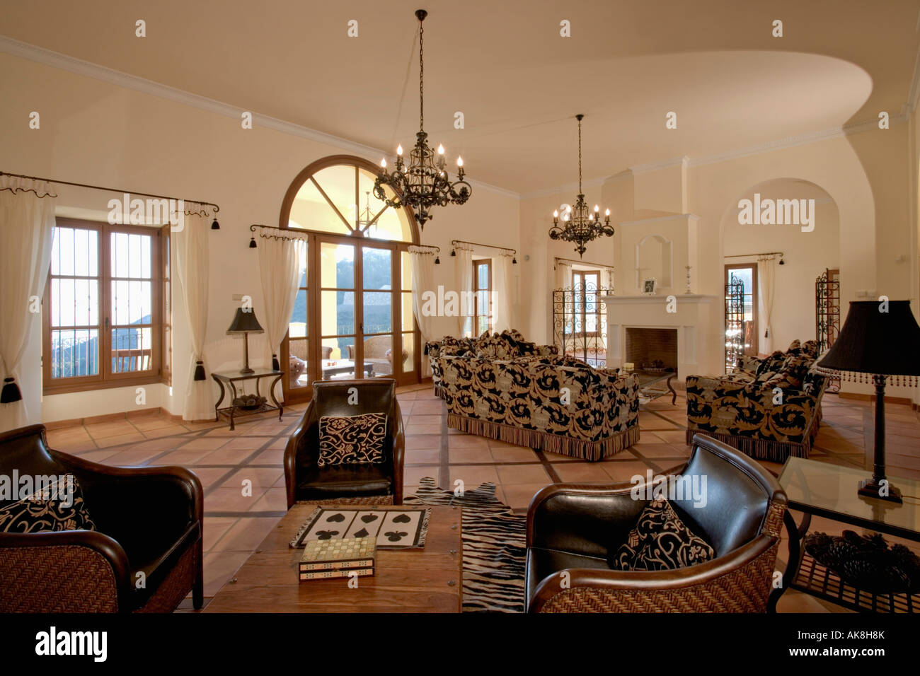 Leather Armchairs And Terracotta Tiled Floor In Large Living Room In Spanish  Villa