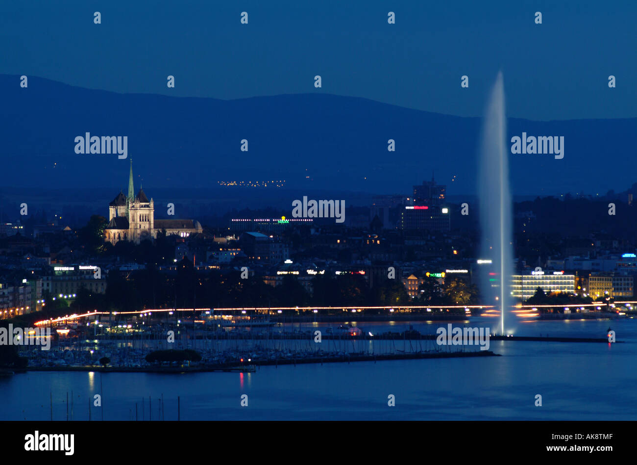 Geneva. Skyline by night witJet d'Eau. Lac Leman and cathedral St. Pierre. - Stock Image