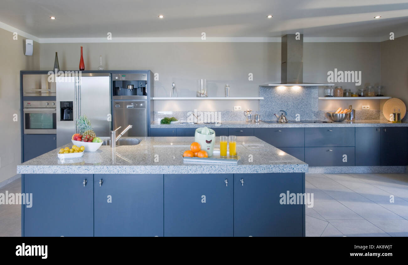 Large modern blue kitchen with island unit and pale grey granite ...