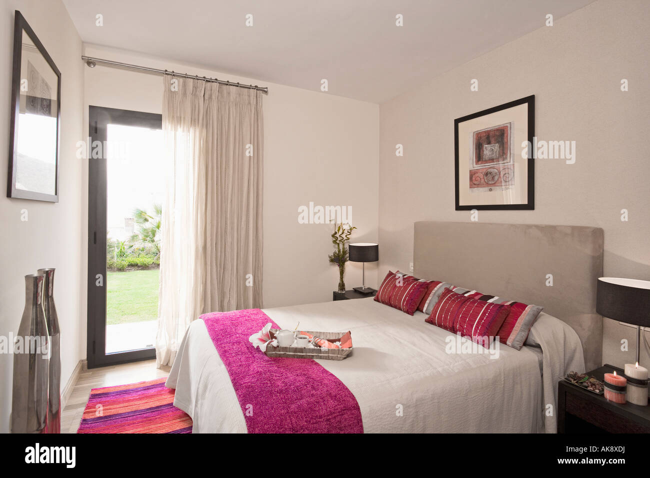 Pink throw and cushions on bed with upholstered grey ...