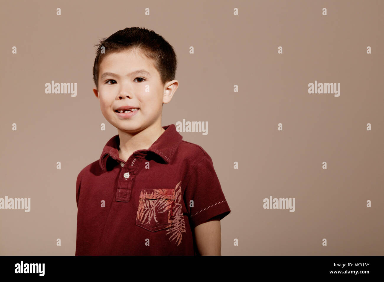 Little boy smiling and posed wearing red shirt - Stock Image
