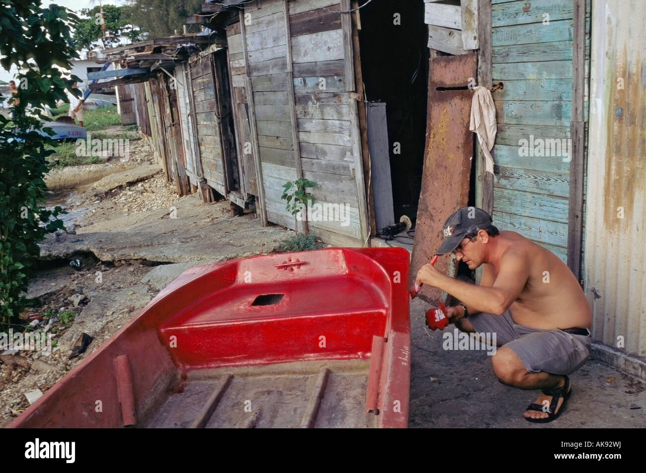 Fisherman painting boat red by the Rio Almendares in Mirimar Havana Cuba Stock Photo