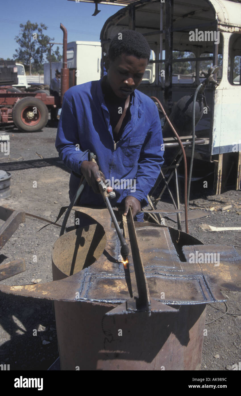 A male black African using and oxyacetalene welder to weld two sheets of metal together to repair a bus Harare Zimbabwe Stock Photo