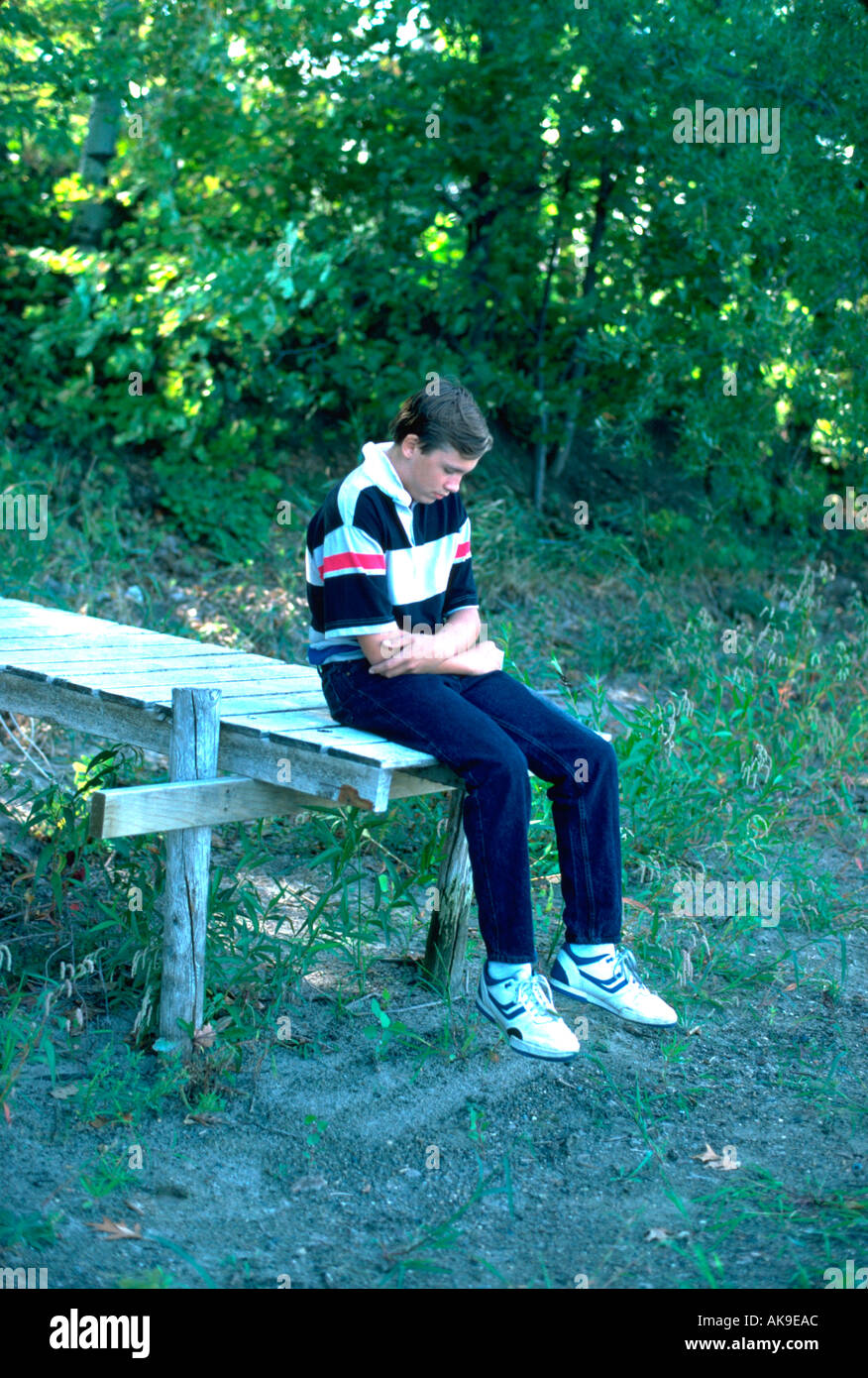 Age 16 teen, deep in thought, sitting on end of dock. Mound Minnesota USA - Stock Image