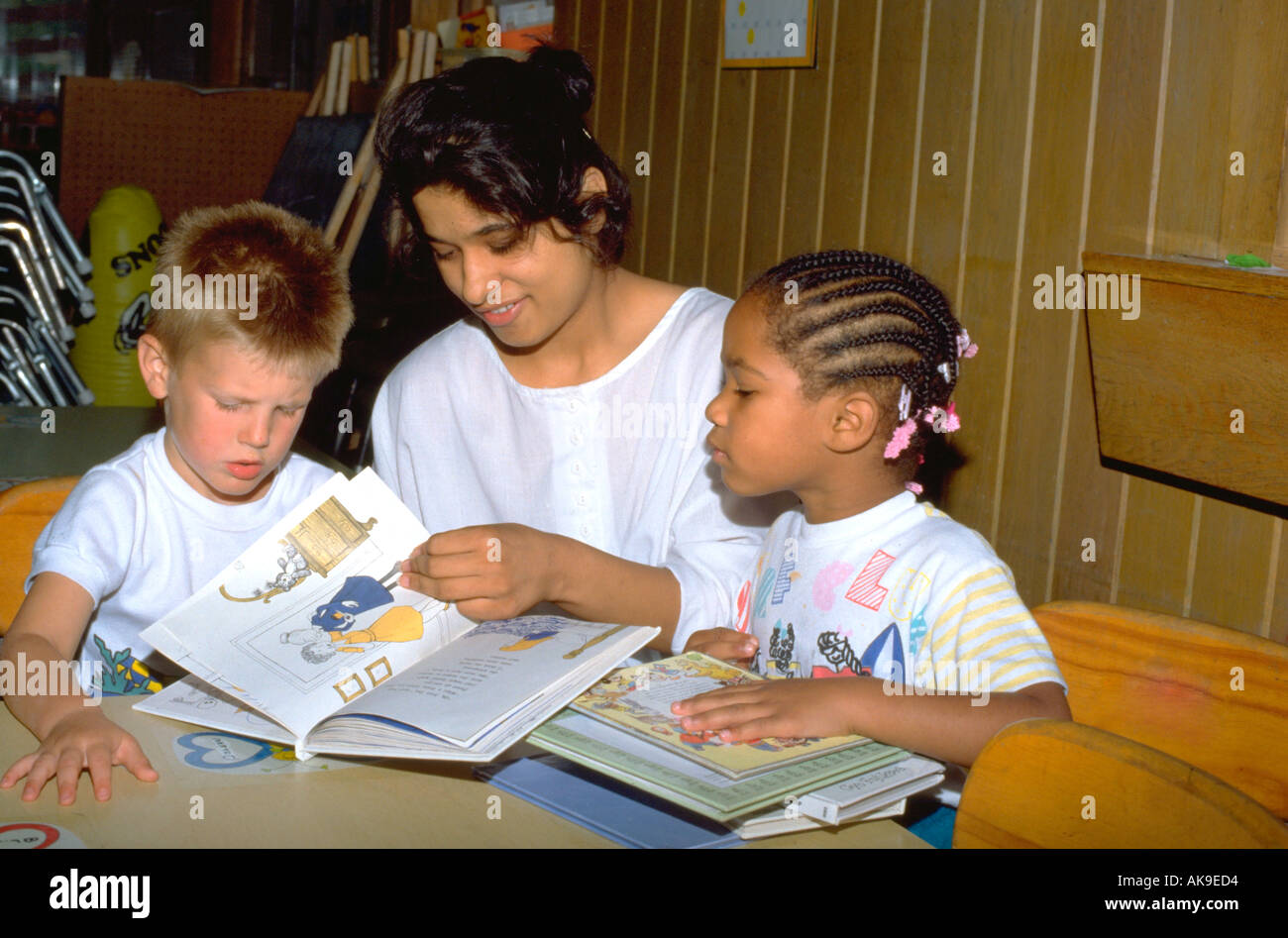 East Indian girl age 19 reading book with two children age 5. St Paul Minnesota USA Stock Photo