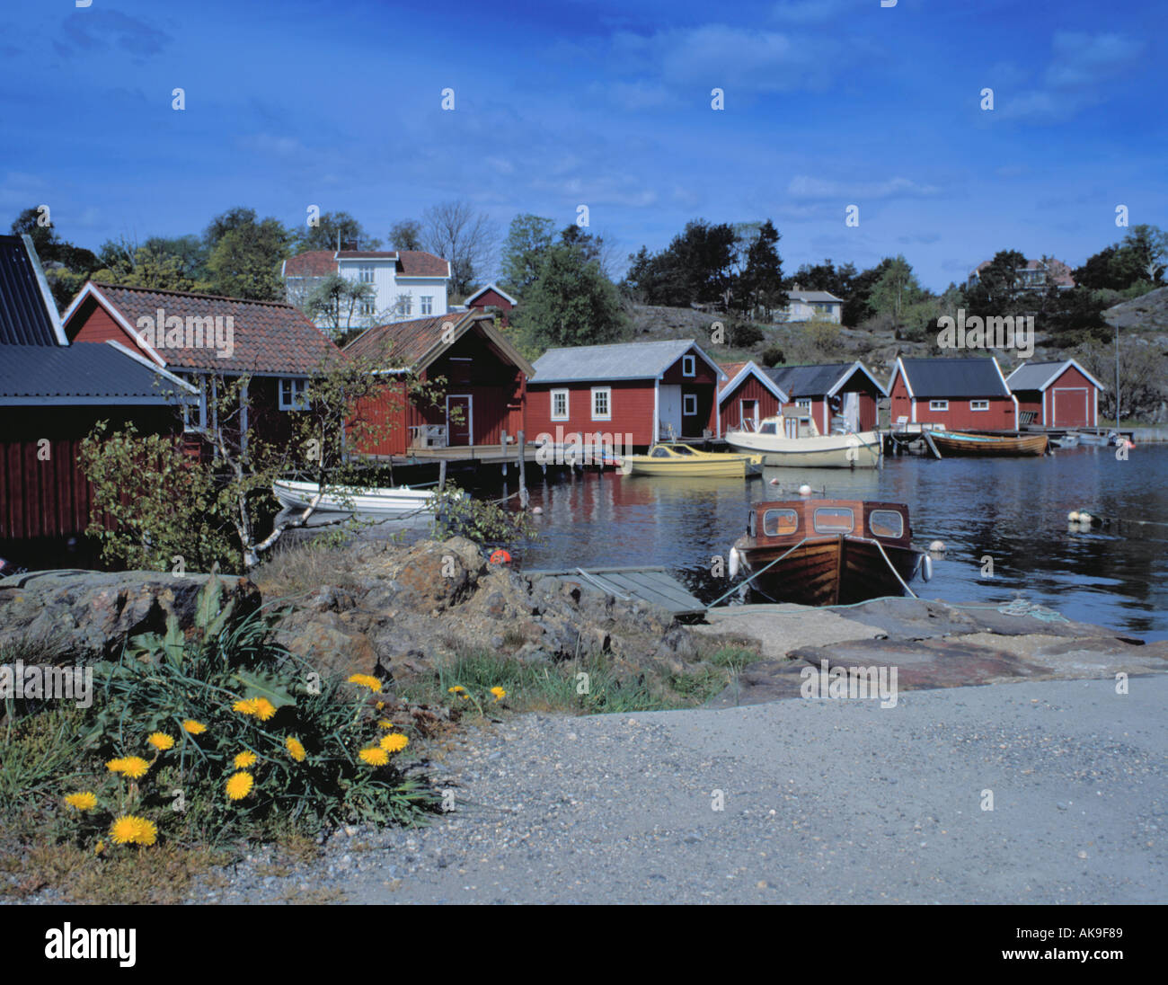 View over harbour to pretty waterside wooden huts, Homborsund, Aust-Agder, Norway. - Stock Image