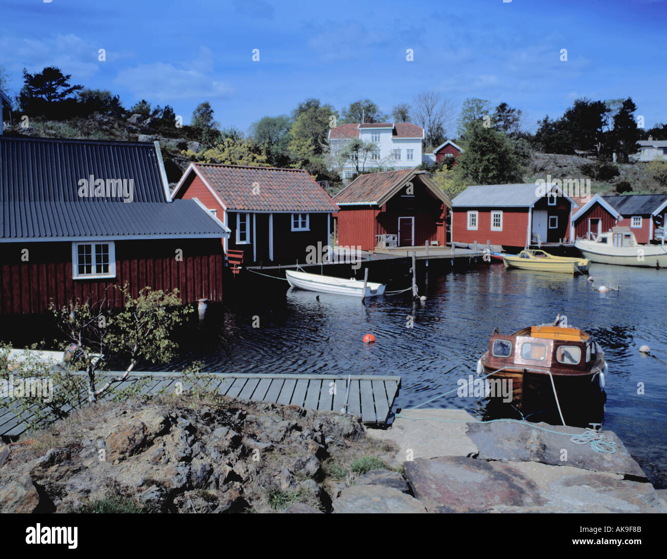 Picturesque view over harbour to waterside wooden huts, Homborsund, Aust-Agder, Norway. - Stock Image