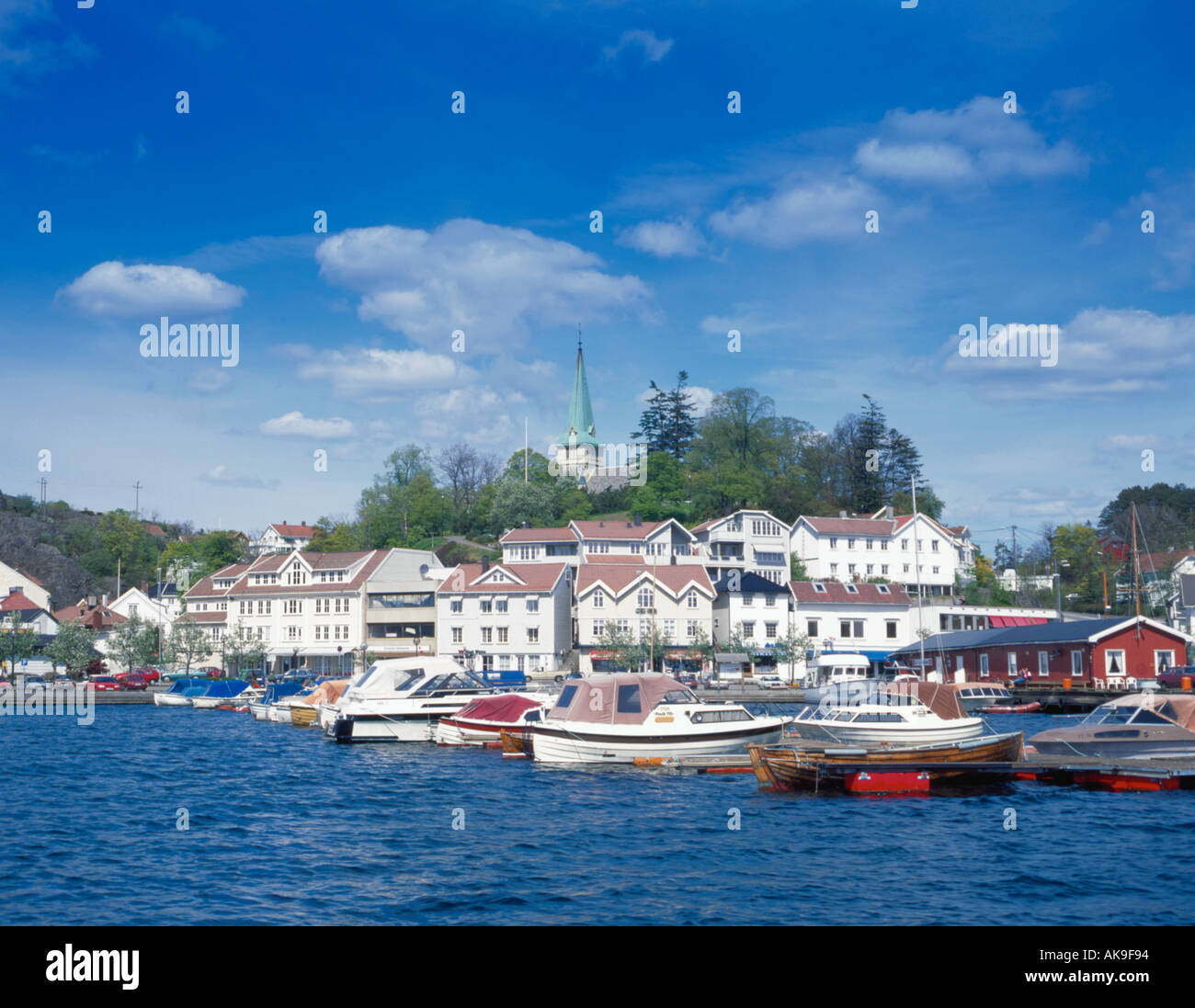 View over boats and harbour to picturesque village of Grimstad, Aust-Agder, Norway. - Stock Image
