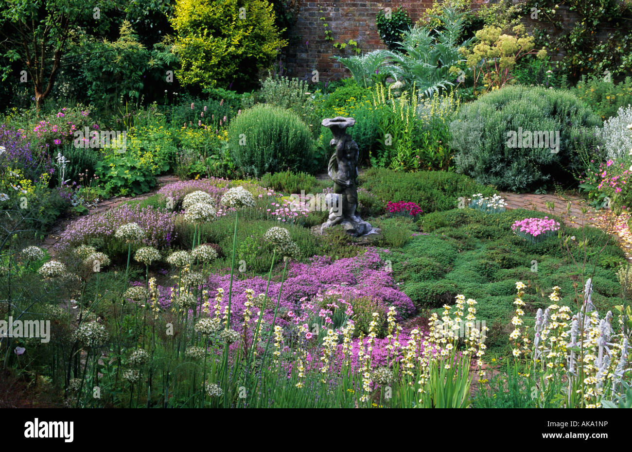 private garden Sussex herb garden with thyme and antique statue sa focal point - Stock Image