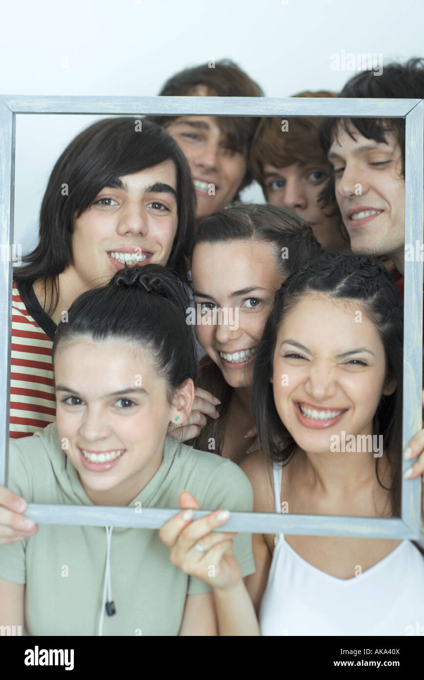 Group of young friends posing for photo, holding up picture frame, smiling at camera, portrait - Stock Image