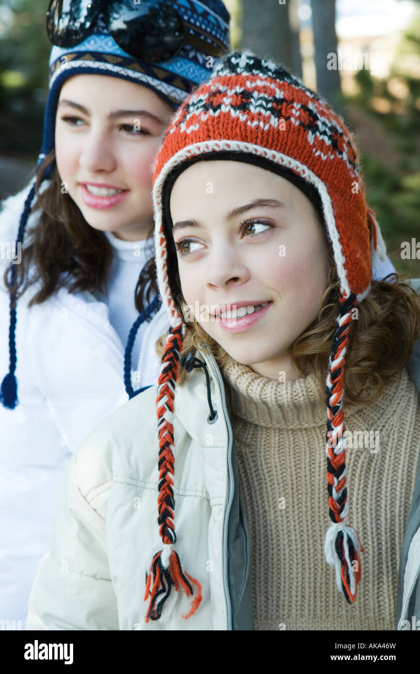 Two teenage girls wearing knit hats, smiling, looking away - Stock Image