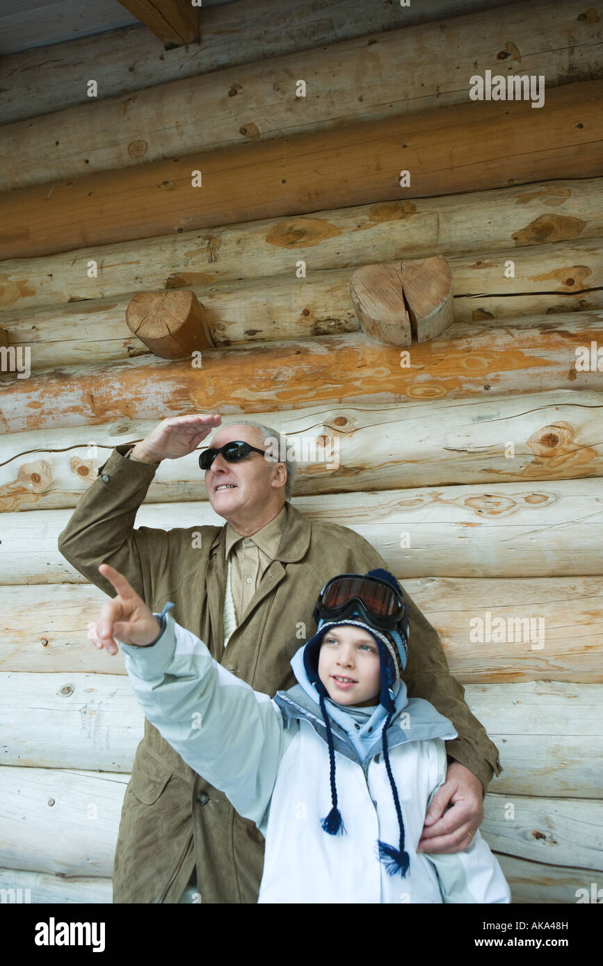 Grandfather and grandson standing together, boy pointing, both looking up - Stock Image