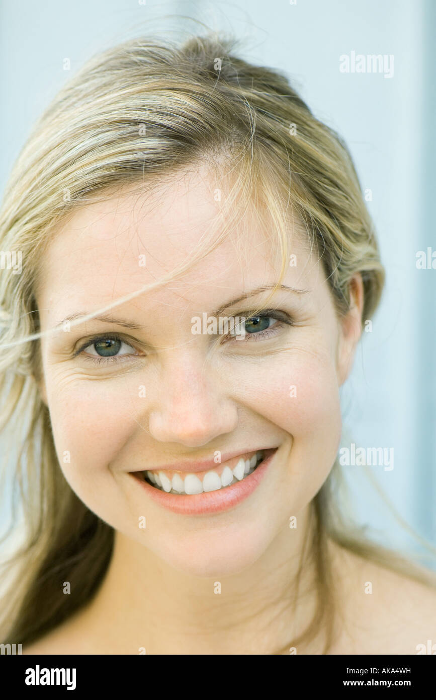 Young woman smiling at camera, tousled hair, portrait - Stock Image